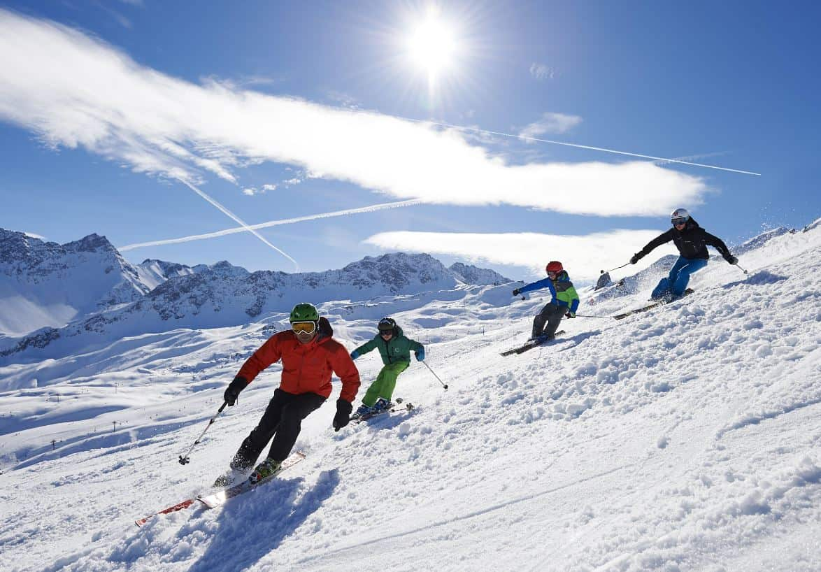 Family skiing on holiday with blue skies