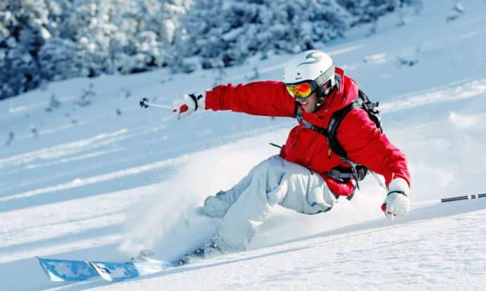 Man in red jacket skiing powder in La Villa, Italy