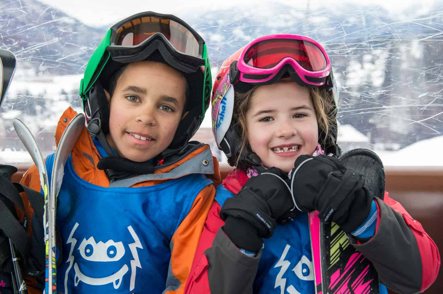 Two children sitting in a ski lift with their goggles off